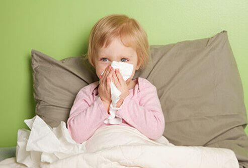 Home remedies for the flu or a cold a young girl is sick in bed with a runny nose altavistaventures Choice Image
