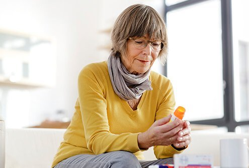 A senior woman examines her prescription bottle.