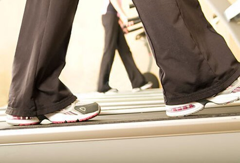A woman warms up on a treadmill.