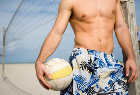 Photo of man on beach with volleyball.
