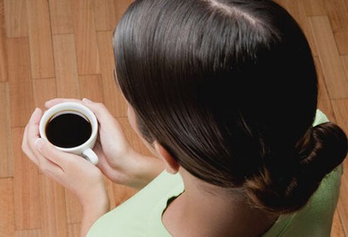 A woman holding a cup of coffee.