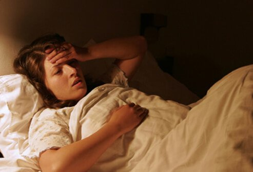 A girl suffering from mono lies in bed.