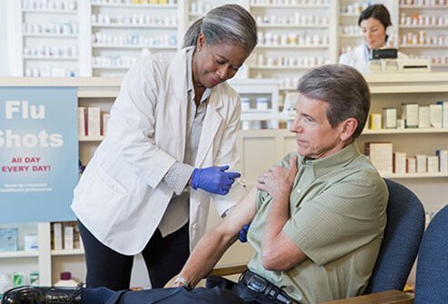 A man receives a flu shot at a pharmacy.