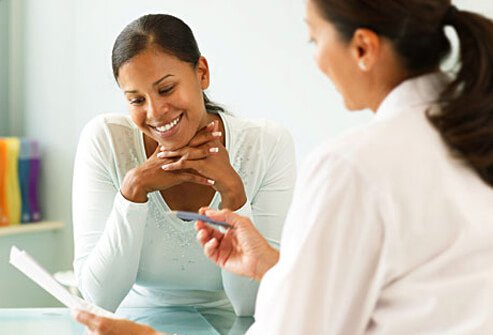 Photo of therapists talking over paper with woman.