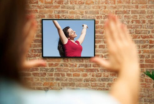 Photo of woman aligning picture on wall.