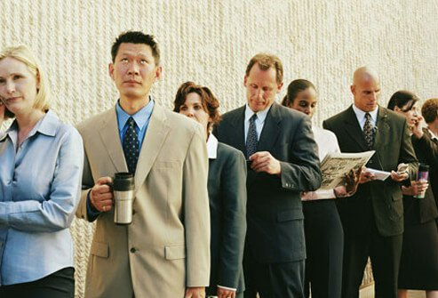 A group of business men and women in line.