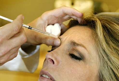 A woman receives a Botox injection to her forehead.