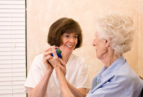A nurse instructs a senior woman on how to exercise.
