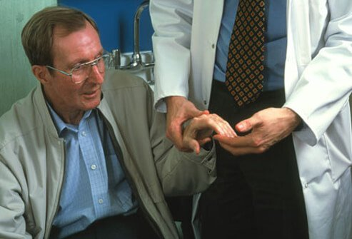 Photo of a patient with Parkinson's being examined by a doctor.