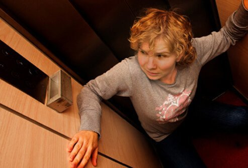 A woman suffers claustrophobia in an elevator.