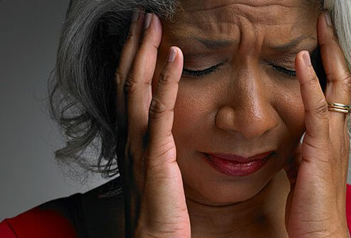 Photo of a depressed woman with a headache.