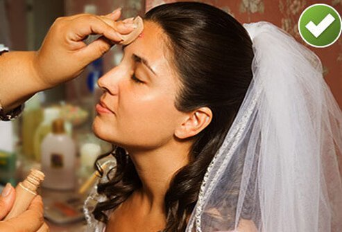 Photo of bride using full coverage concealer.