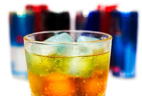 A glass and several bottles of energy and sports drinks.