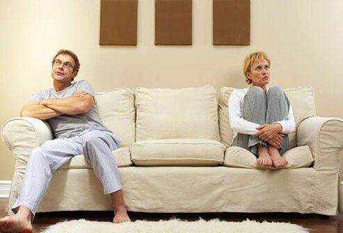 An arguing couple sitting on a sofa.