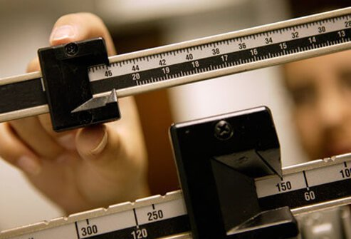 A woman checking her weight on a scale.