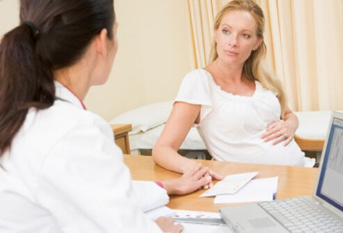 Photo of pregnant woman with doctor discussing the risks of shingles while pregnant.