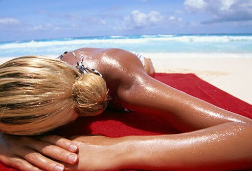 Woman tanning on sunny beach, at risk for skin cancer.