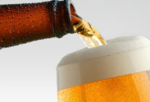 Pouring a light beer into a glass.