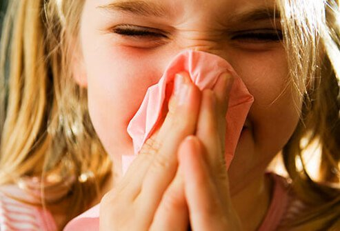 A girl with a cold blowing her nose.