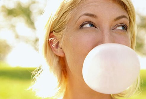 A woman blowing a big bubble.