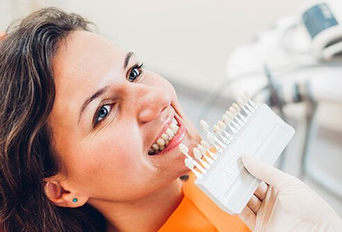 A dentist compares shades of whiteness to a patient's teeth.