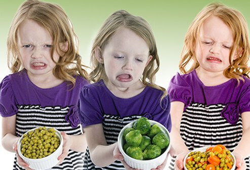 A young girl is grossed out by the taste of vegetables.