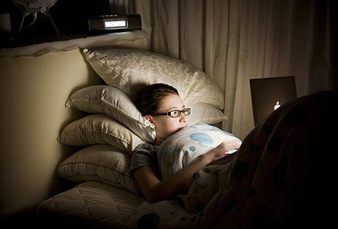 Photo of teen sitting up late on computer.