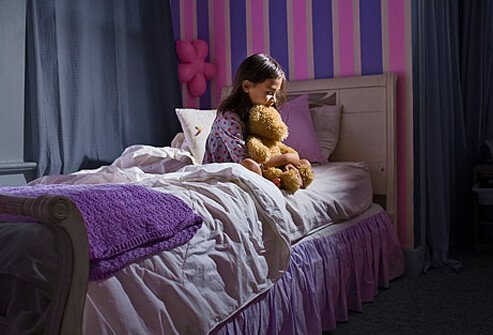 Photo of little girl sitting awake at night with worries.