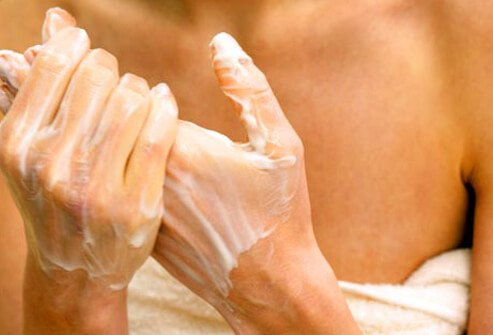 Photo of woman applying moisturizer.