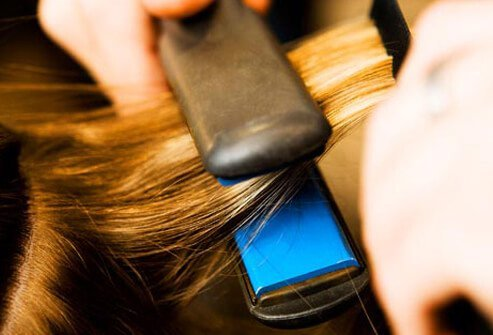 Photo of flat iron pressing hair.