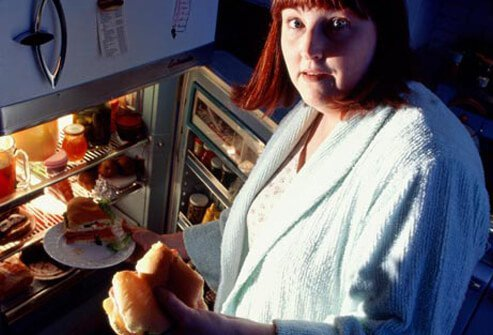 A woman shows signs of binge eating at night.
