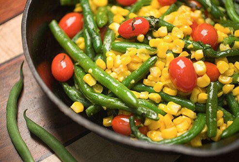 Vegetable stir-fry being served onto a plate.