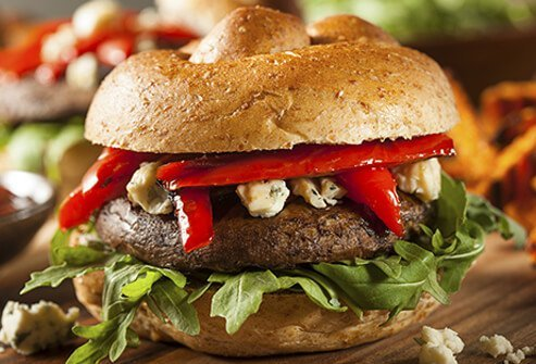 Portobello mushroom burger topped with lettuce, onions, and tomatoes.
