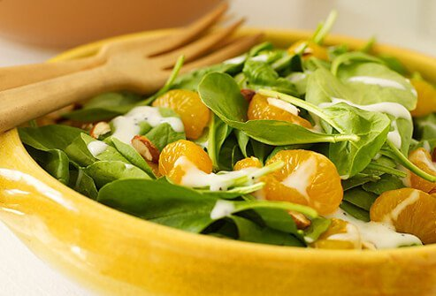 Spinach salad topped with dressing, almonds, and mandarin oranges.