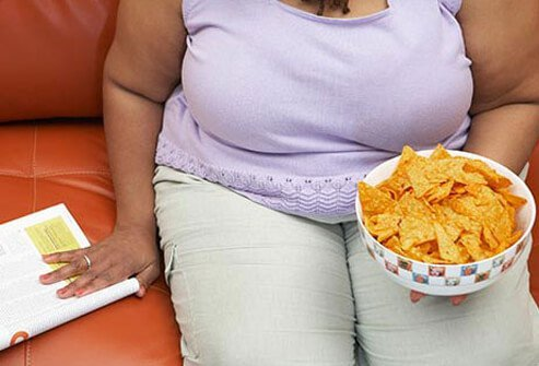 An woman binge eating a bowl of nacho cheese corn chips.