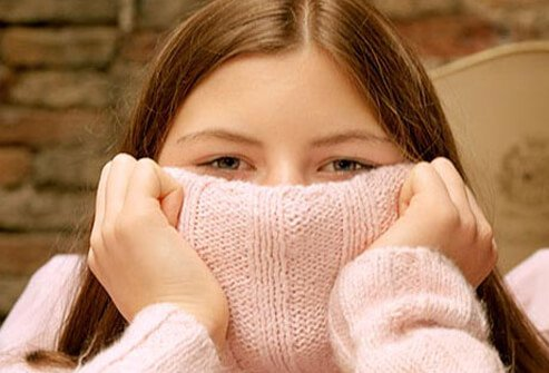 A woman hiding her face with her sweater.